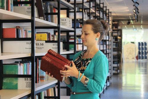 Bibliothekarin sortiert Bücher ein